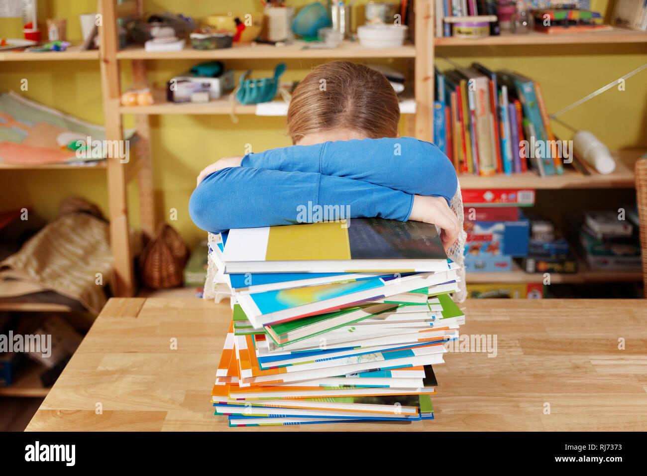 Mädchen, 10 Jahre alt, bei den Hausaufgaben, lehnt über einem Stapel Bücher, überfordert - Stock Image
