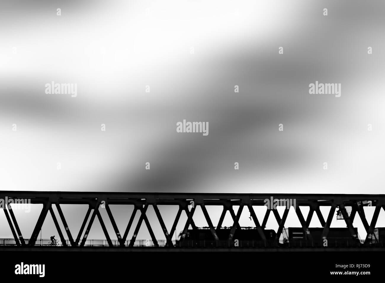 Silhouette einer Eisenbahnbrücke mit einem Zug und Fahrradfahrer, - Stock Image