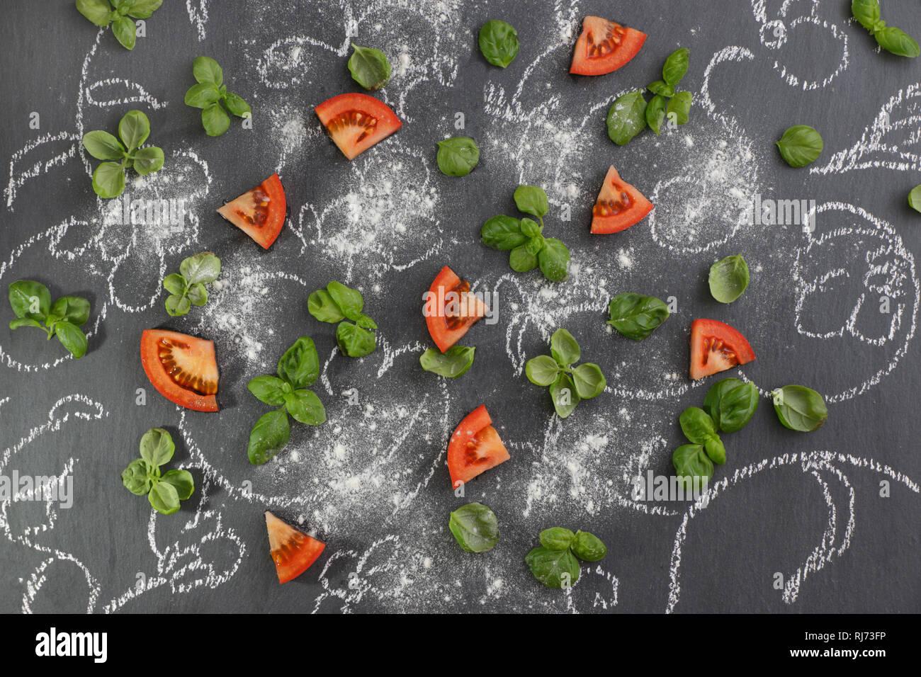 Tomaten mit Basilikum auf mit Kreide bemalter Tafel Stock Photo