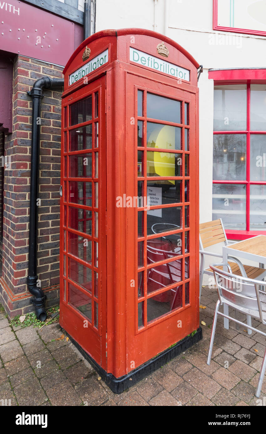 Public Access Defibrillator machine in an old red telephone box in Storrington, West Sussex, England, UK. - Stock Image