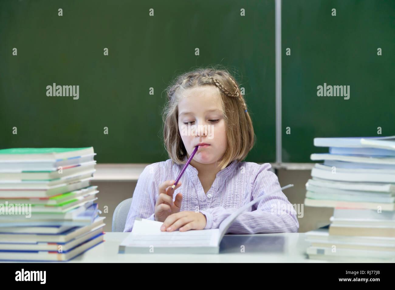 Schülerin, 7 Jahre alt, lesend, zwischen zwei Stapeln Bücher, vor einer Tafel Stock Photo