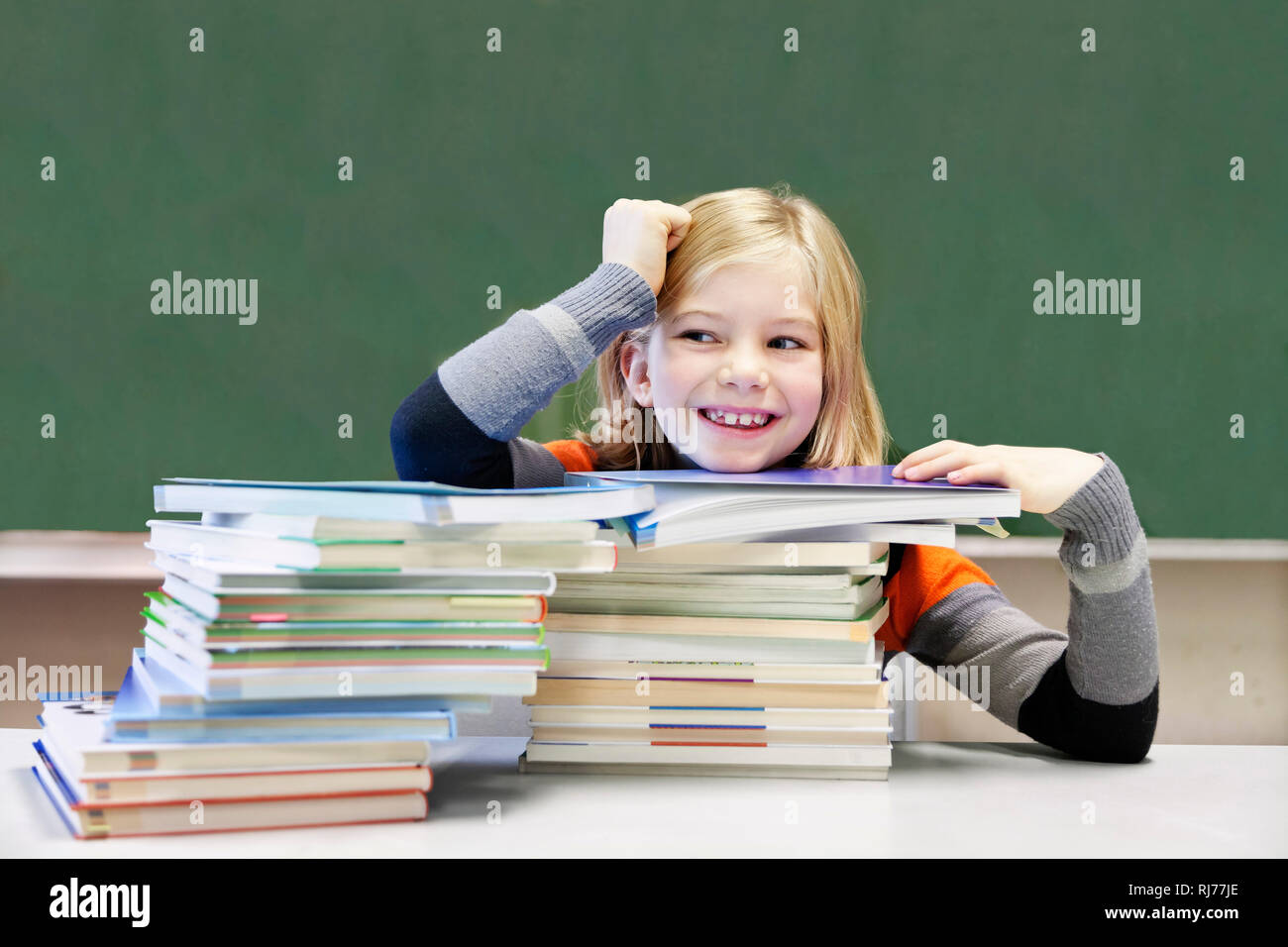 Schülerin, 9 Jahre alt, lächelnd vor zwei Stapeln Bücher vor einer Tafel Stock Photo
