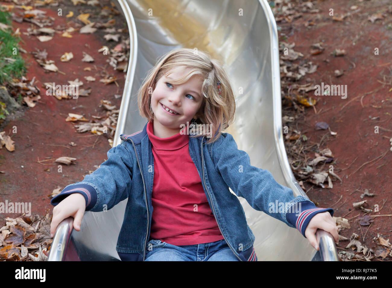 Siebenjähriges Mädchen auf einem Kinderspielplatz auf einer Rutsche Stock Photo