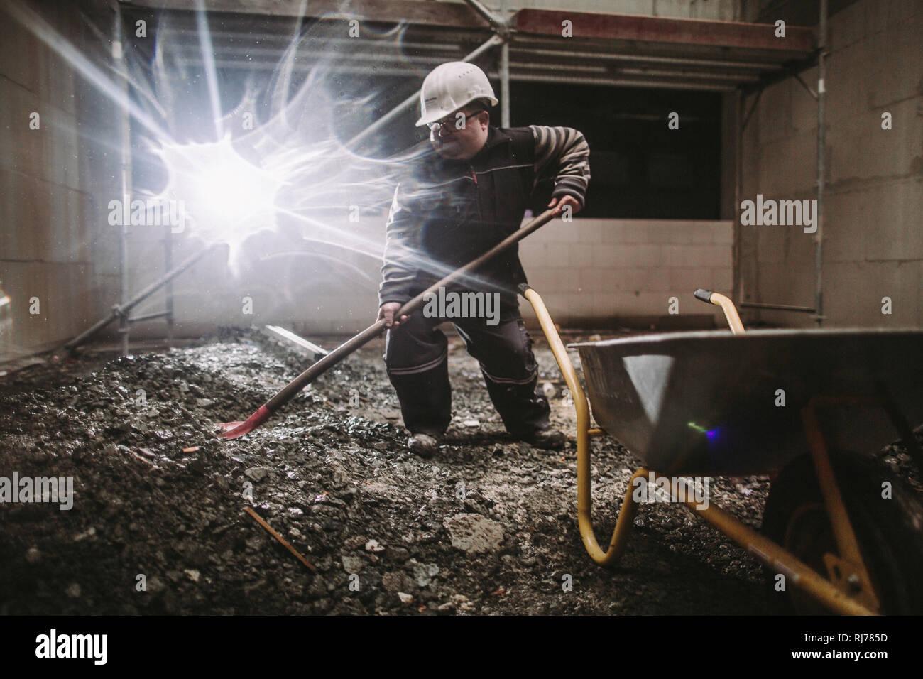 Geistig- und körperlich behinderter Hausmeister bei der Arbeit - Stock Image