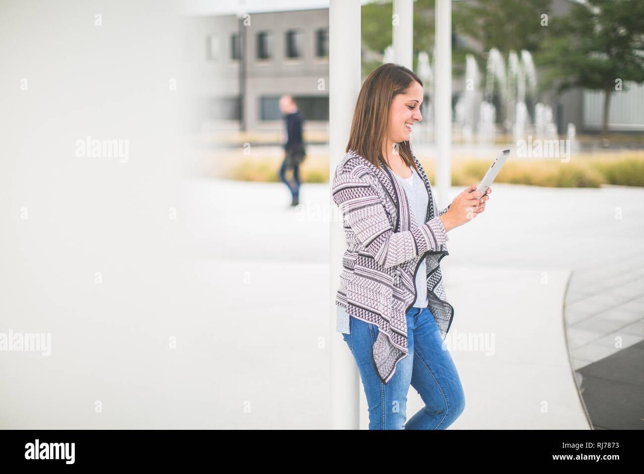 Junge Frau mit Tablet unterwegs Stock Photo