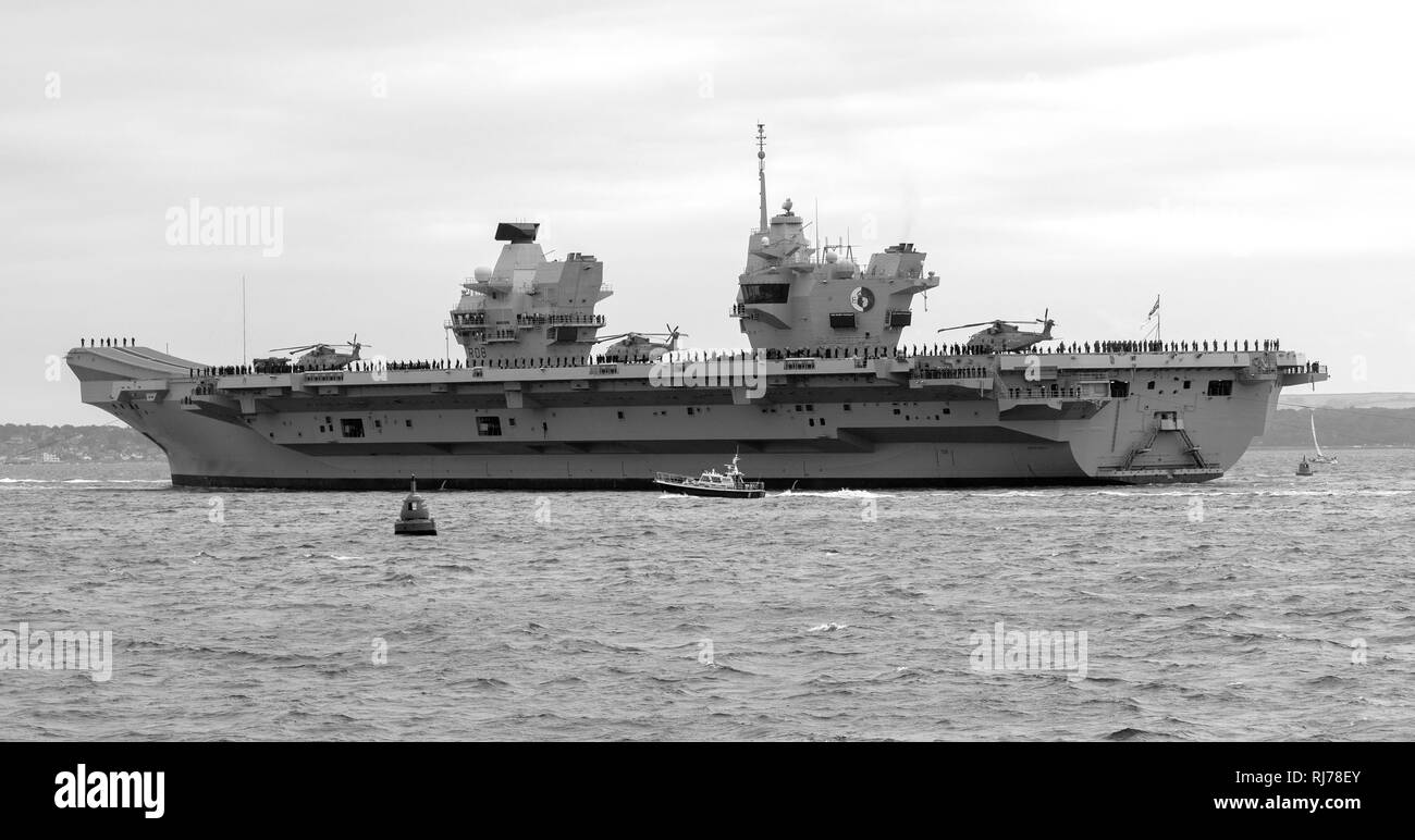 Royal Navy aircraft carrier HMS Queen Elizabeth leaving Portsmouth on route to the USA, Portsmouth, Hampshire, England, UK - Stock Image