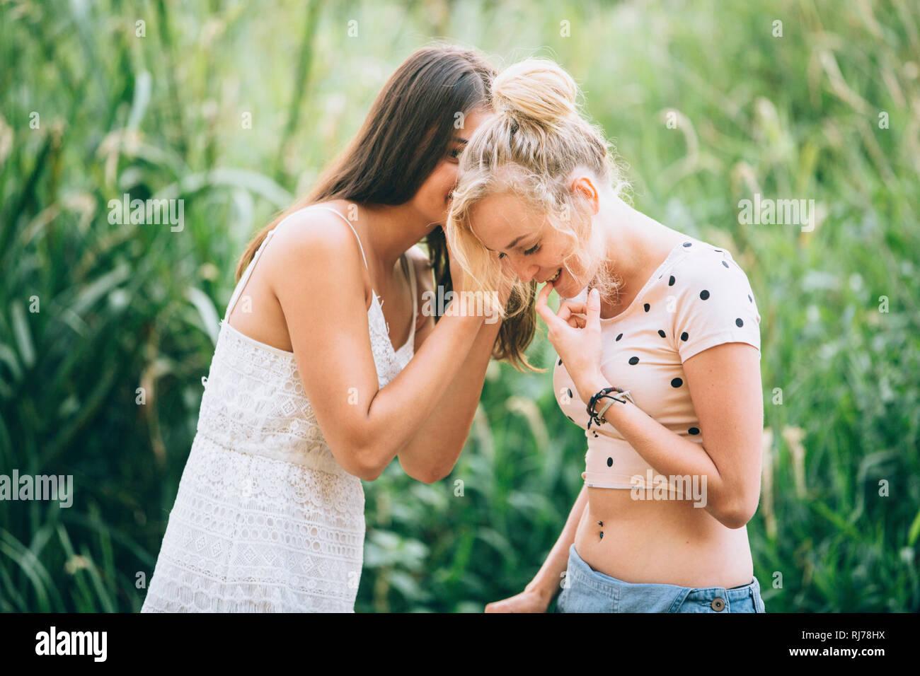 Eine junge Frau flüstert ihrer Freundin etwas ins Ohr Stock Photo