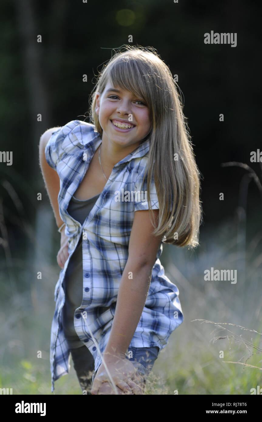 12 jähriges Mädchen mit langen blonden Haaren steht lachend auf einer Wiese mit hohen Gräsern, Hintergrund Unscharf Stock Photo