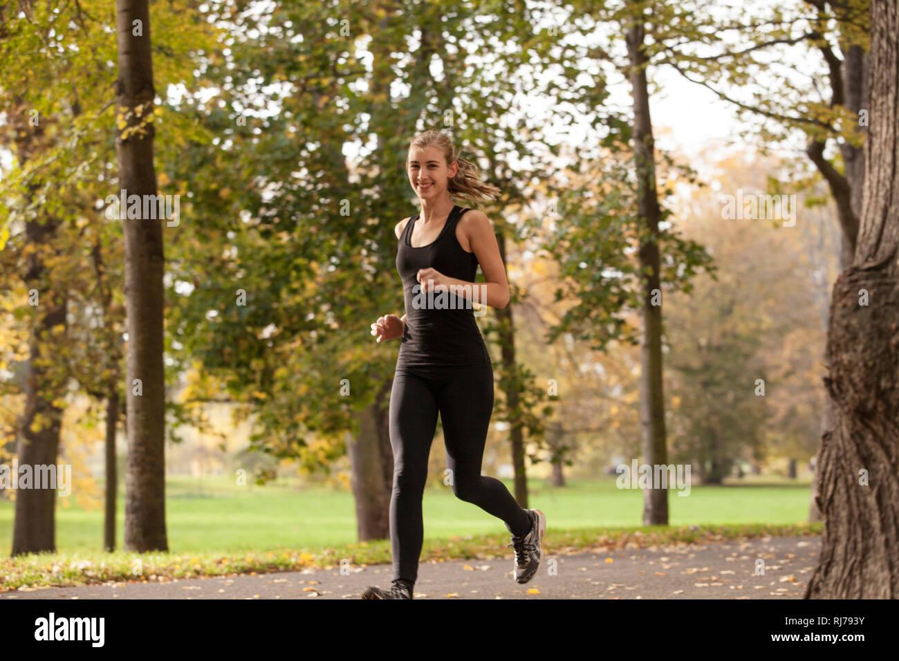junge Frau joggt durch Park - Stock Image