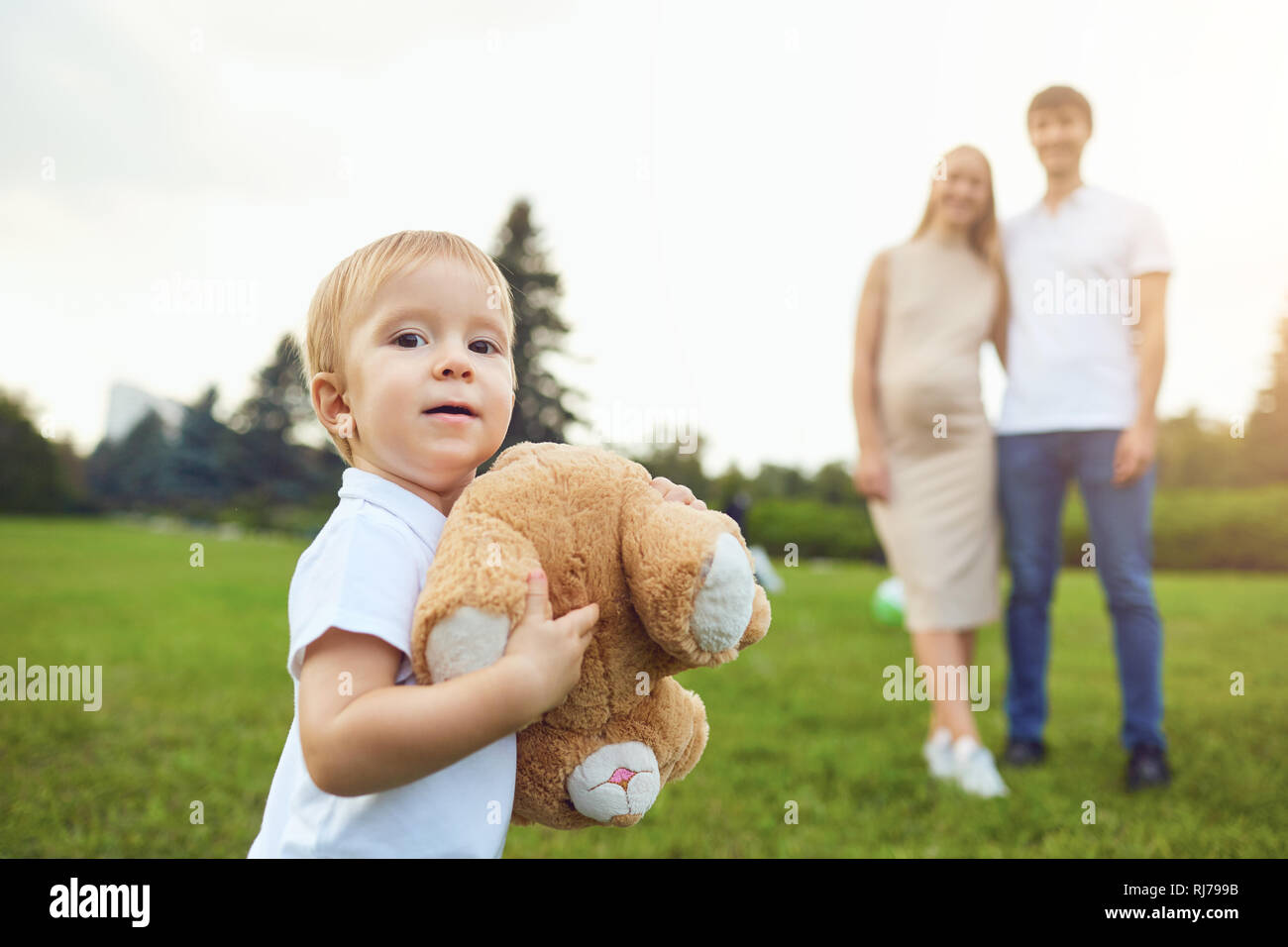 Adorable boy carrying toy in park with parents Stock Photo