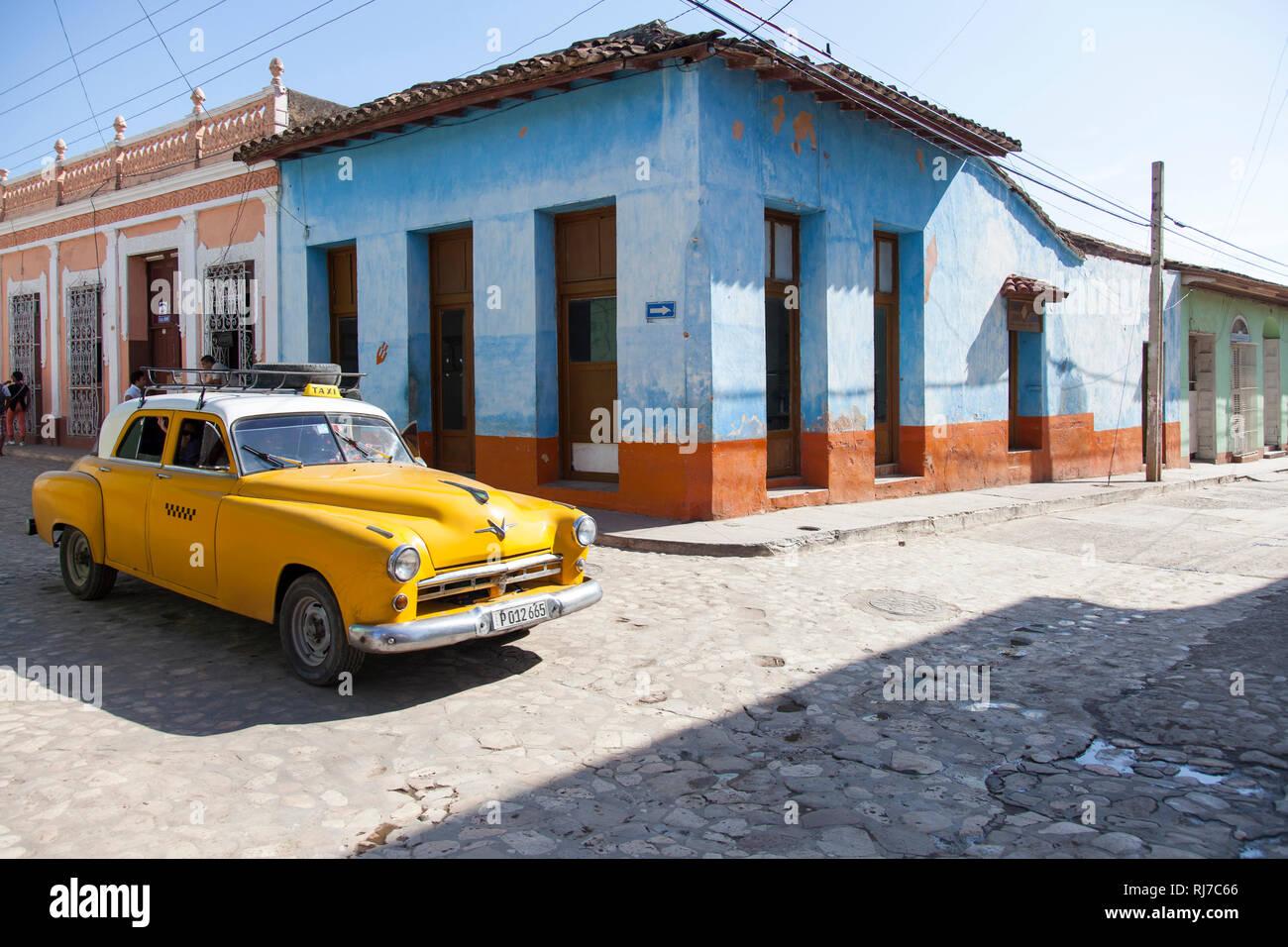 Karibik, Cuba, Kuba, Trinidad, gelber Oldtimer an Straßenkreuzung - Stock Image