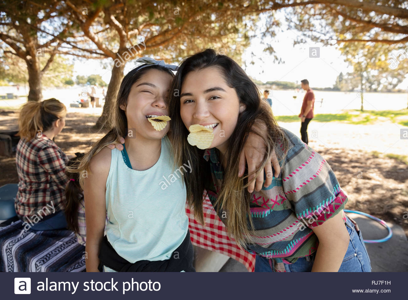 Portrait playful Latinx teenage girls making a face in park - Stock Image
