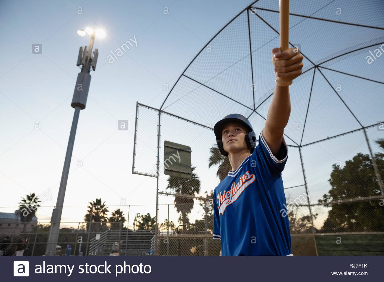 Determined baseball player at bat on field at night - Stock Image