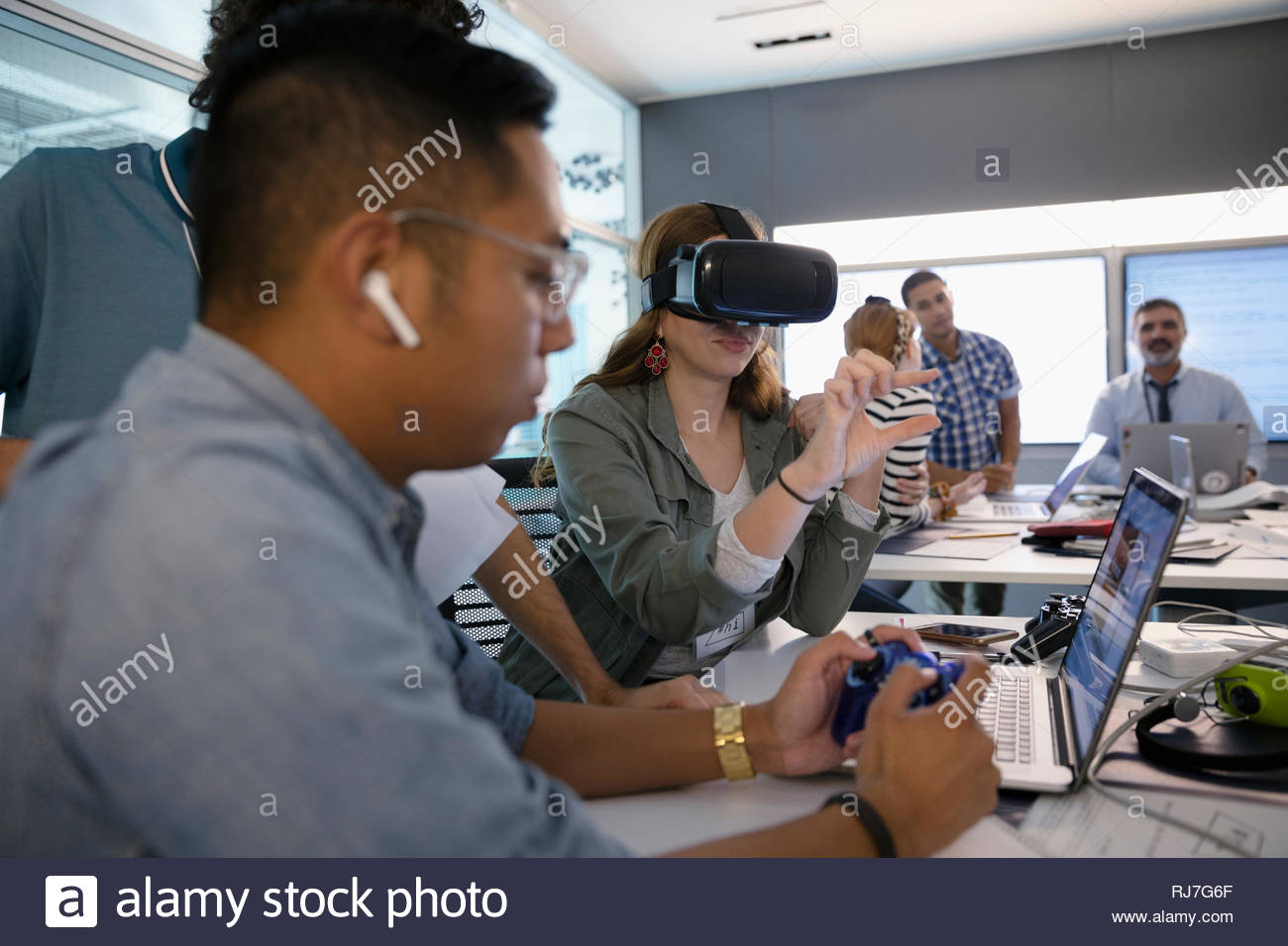 Computer programmers testing virtual reality simulator in office - Stock Image