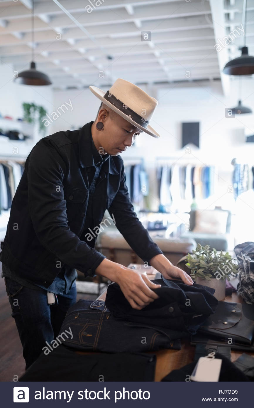 Male business owner arranging display in menswear clothing shop - Stock Image
