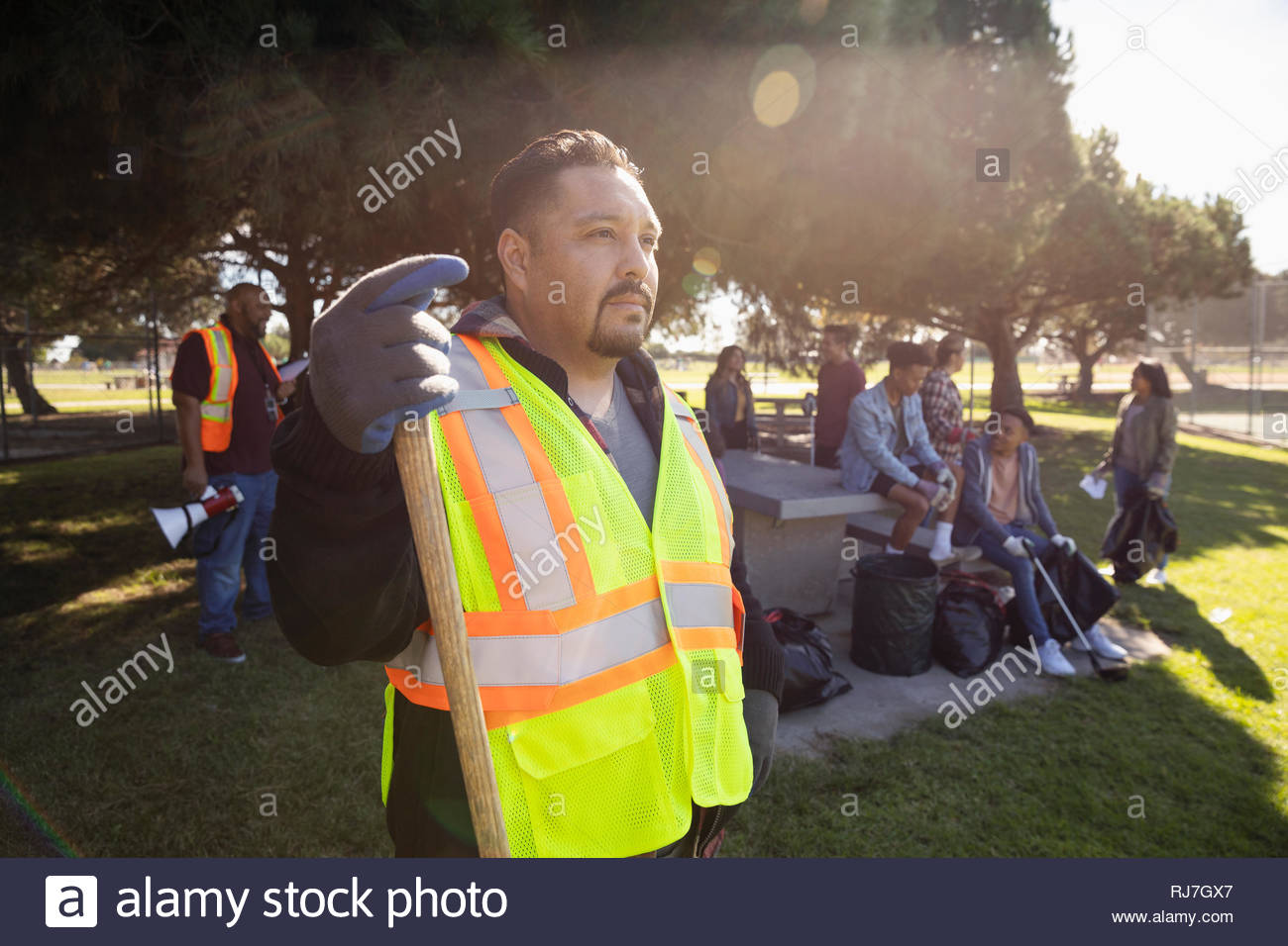 Focused volunteer in reflective vest cleaning park - Stock Image