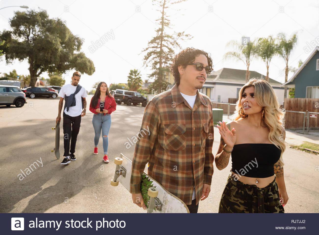Latinx couples with skateboard walking in sunny neighborhood - Stock Image