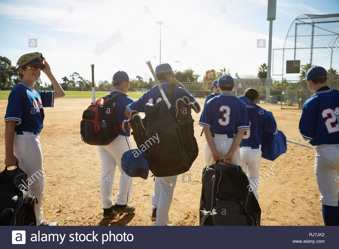 Baseball players carrying equipment on sunny field - Stock Image