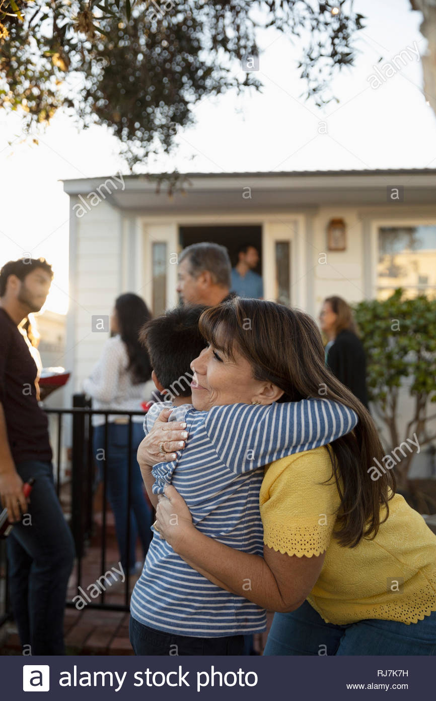 Latinx grandmother and grandson hugging in front yard - Stock Image