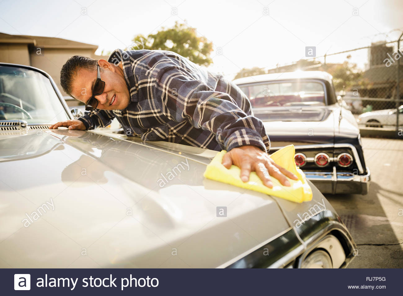 Latinx man waxing vintage car in sunny parking lot - Stock Image