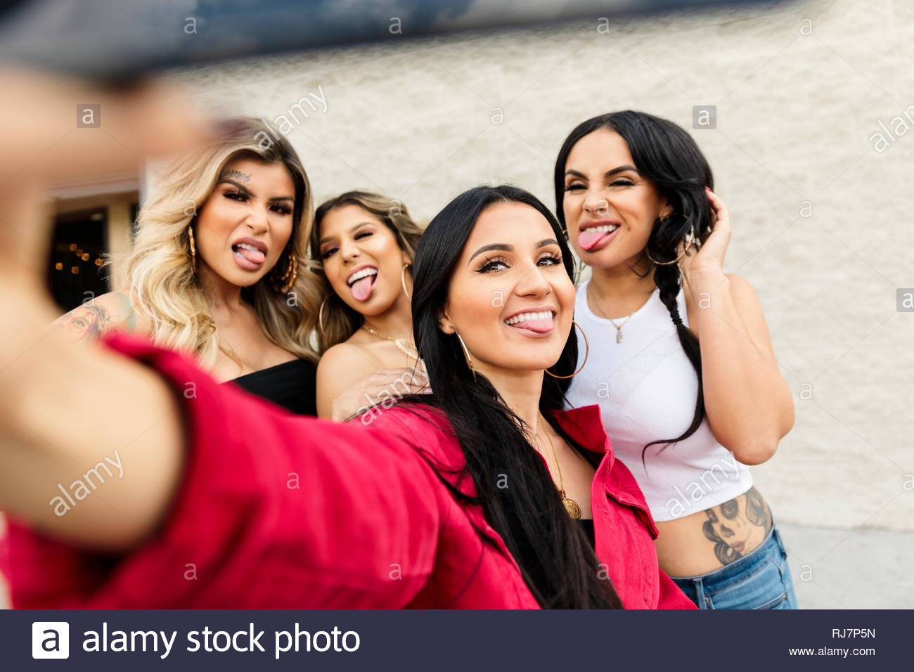 Latinx women friends sticking tongues out, taking selfie Stock Photo