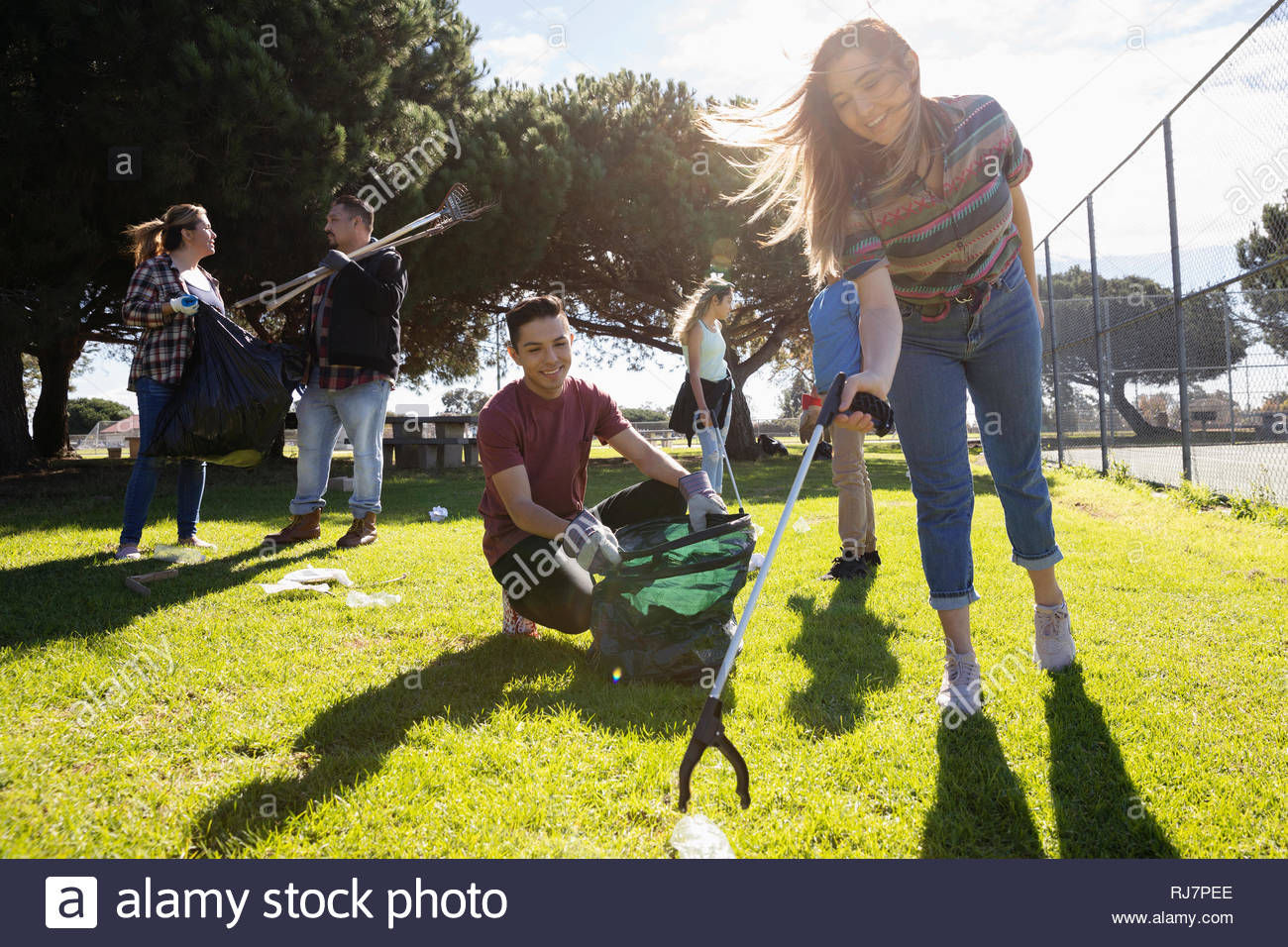 Volunteers picking up garbage in sunny park Stock Photo