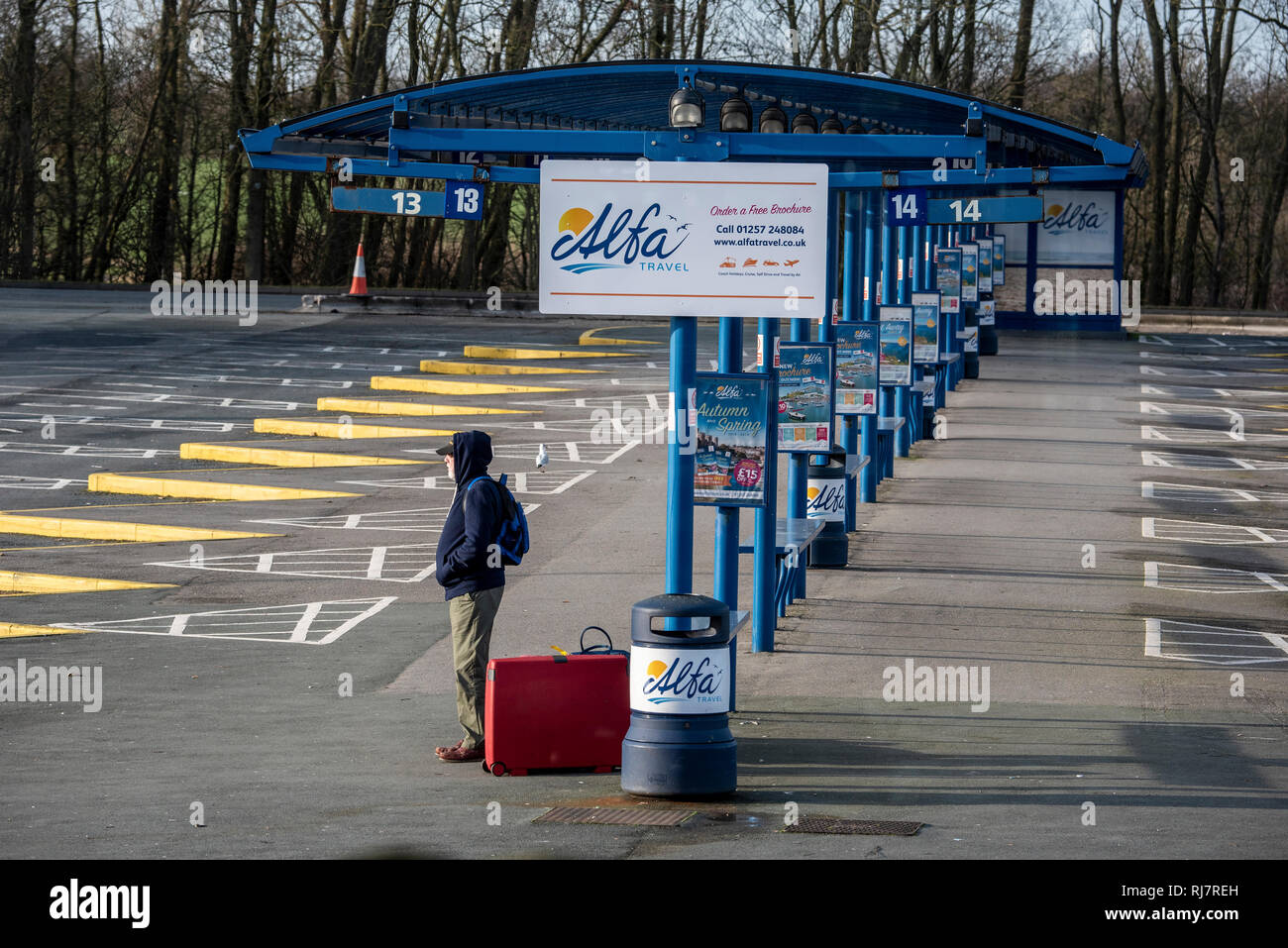 Man waiting for a bus at bus shelter. - Stock Image