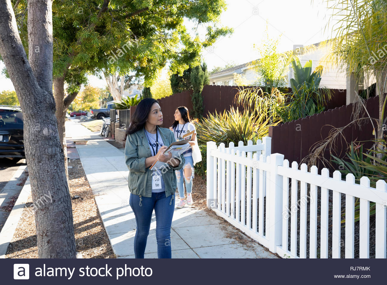 Latinx female volunteers canvassing voters in neighborhood - Stock Image