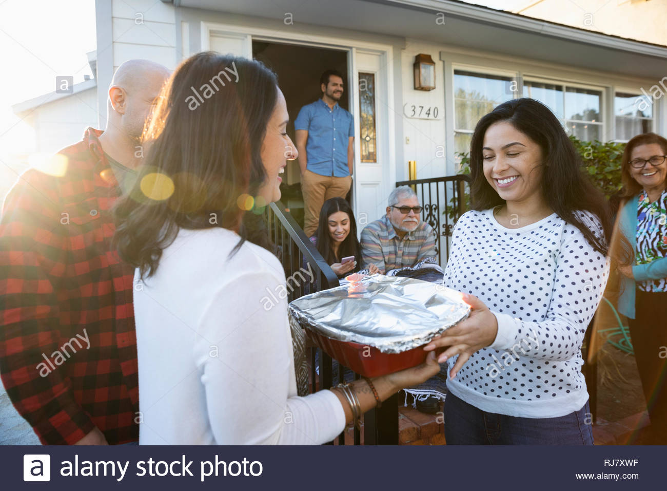 Latinx woman delivering casserole to neighbor - Stock Image