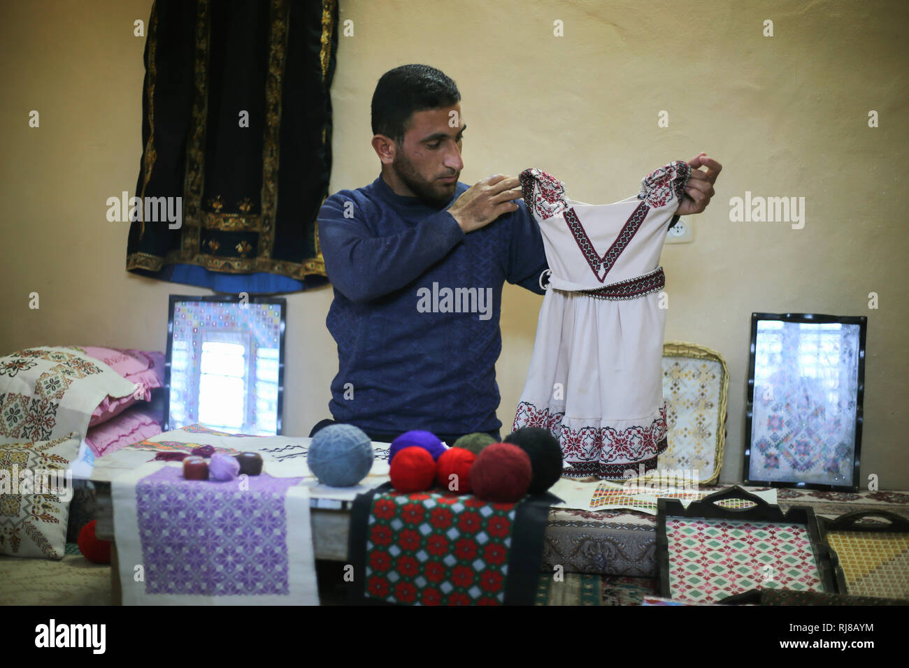 Suleiman seen looking at a dress during as he works.  Palestinian young man Suleiman Abu Taima 23 years inherited the embroidery profession from his mother and work in the absence of job opportunities and the worsening economic situation and the siege on the Gaza Strip. - Stock Image