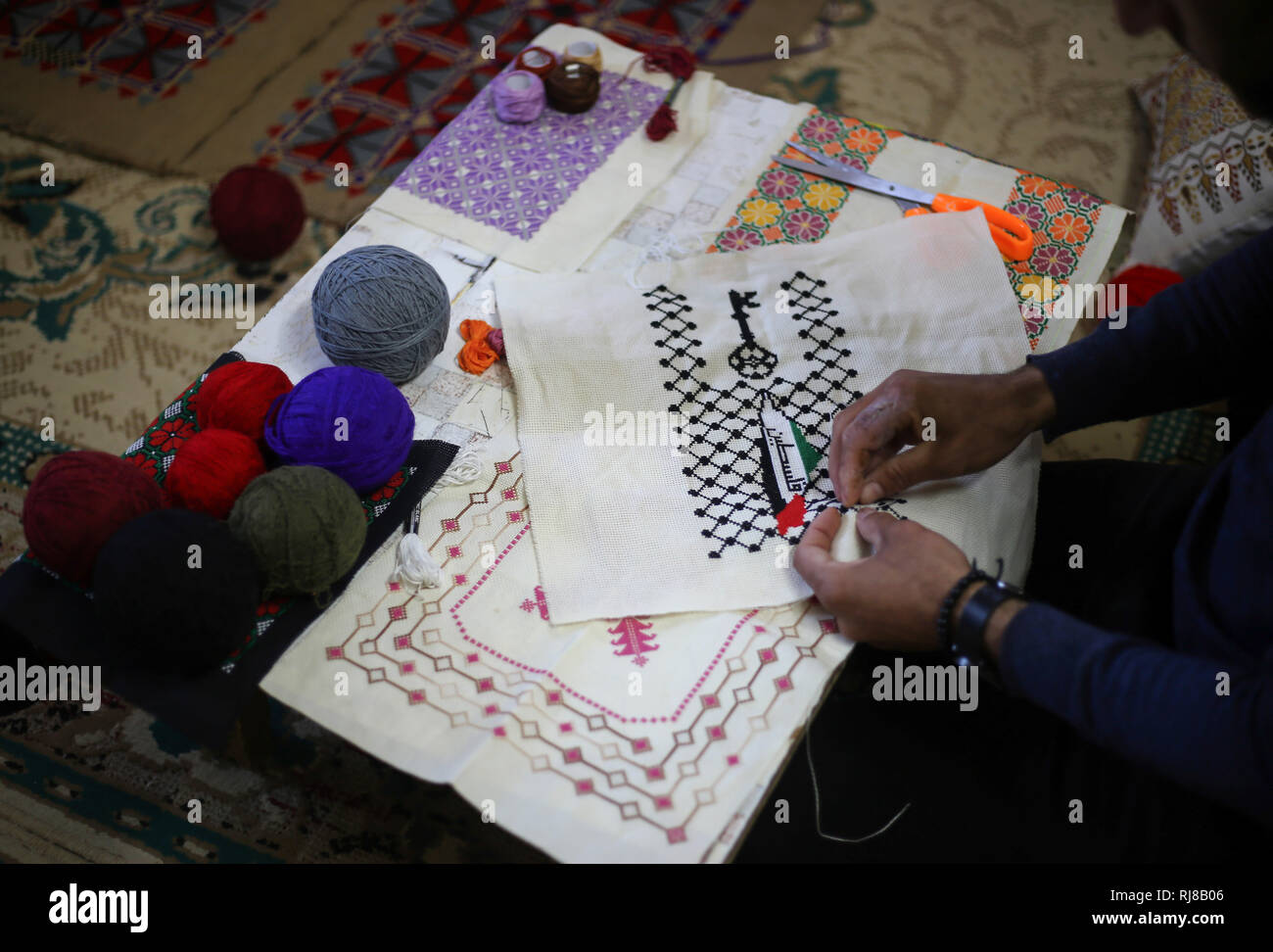 Suleiman Abu seen doing embroidery work.  Palestinian young man Suleiman Abu Taima 23 years inherited the embroidery profession from his mother and work in the absence of job opportunities and the worsening economic situation and the siege on the Gaza Strip. - Stock Image