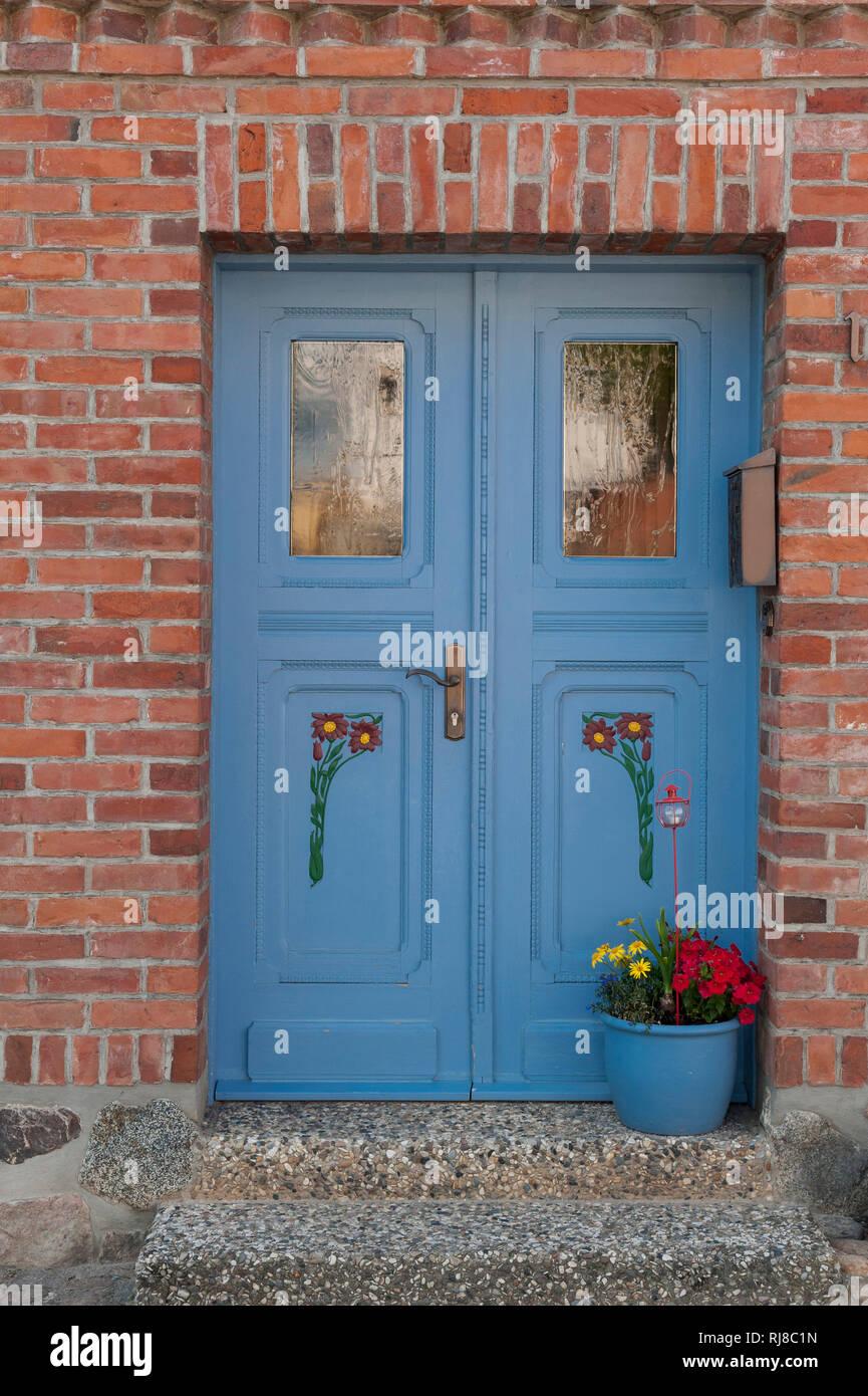 mit Blumen verzierte blaue Haustür in rotem Backsteingebäude, am Müritz See - Stock Image