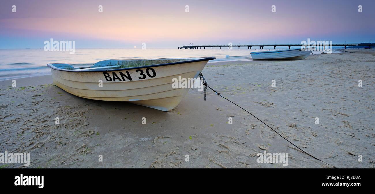 Deutschland, Mecklenburg-Vorpommern, Insel Usedom, Ostseebad Bansin, Fischerboote am Strand bei Sonnenaufgang, hinten die Seebrücke - Stock Image