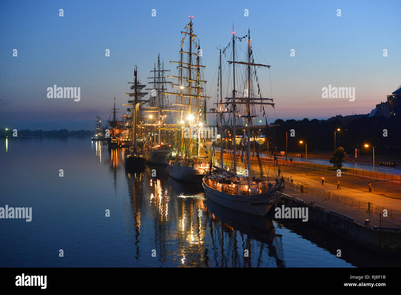 The world largest tall ships berthed in port of Riga, Latvia. Daugava river. Summer night. Dawn. - Stock Image