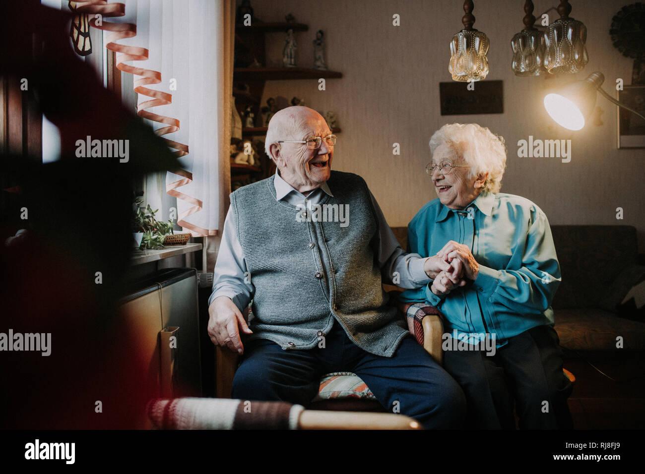 Seniorenpaar sitzt lachend im Wohnzimmer Stock Photo