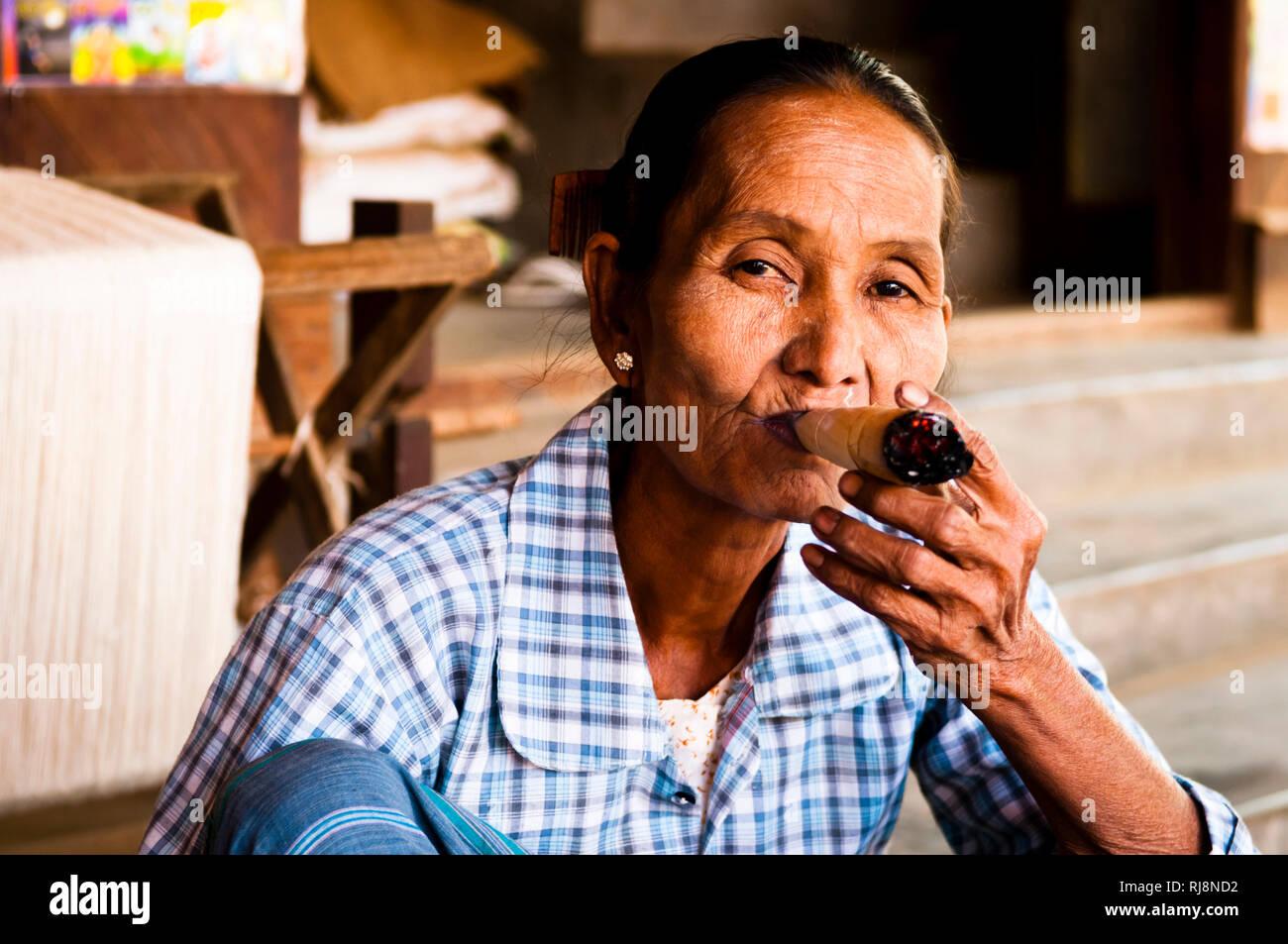 alte Frau beim Rauchen in einem Dorf in Altbagan - Stock Image