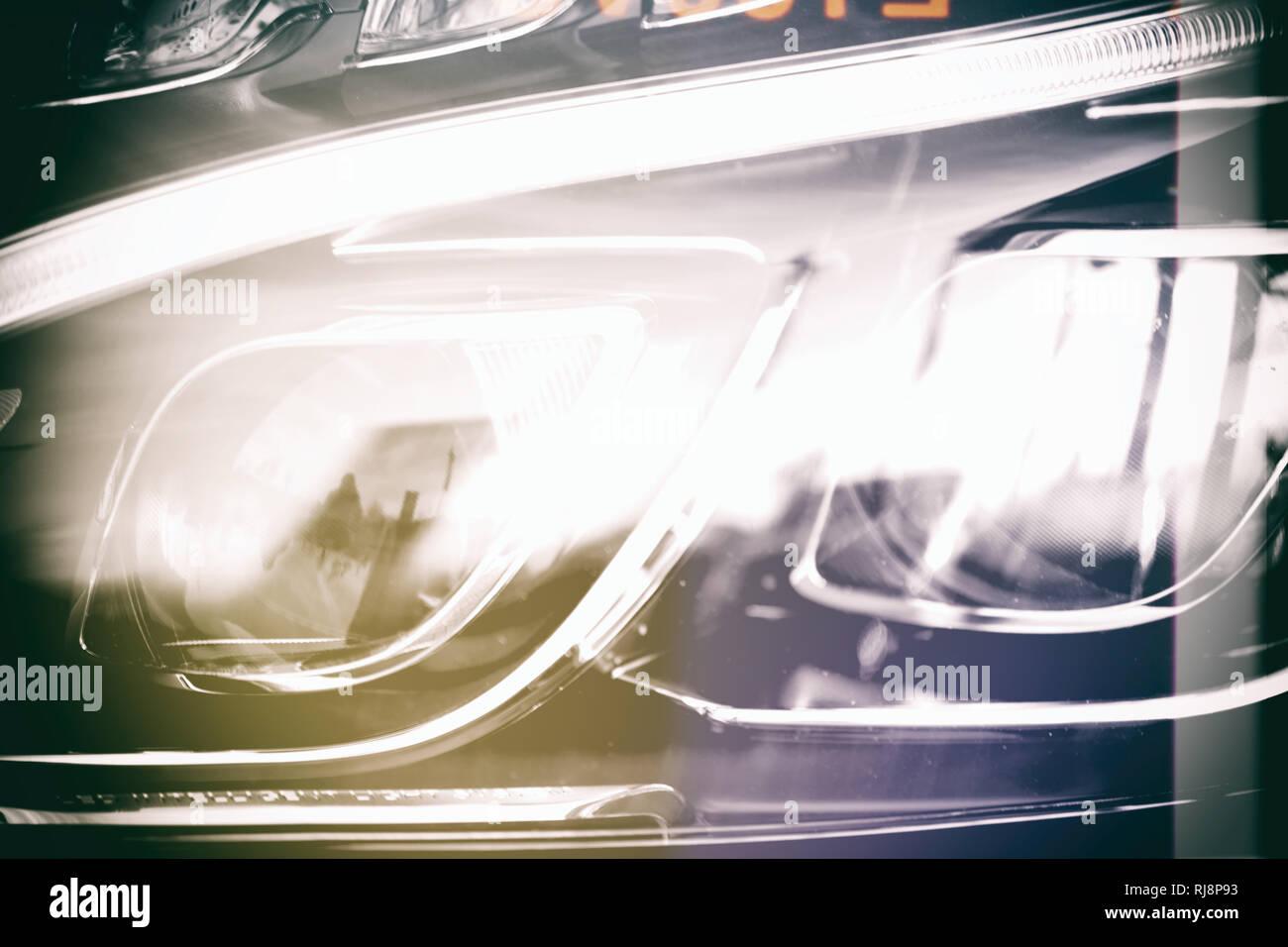 Nahaufnahme des Frontlichtes eines Kraftfahrzeuges mit Neonscheinwerfern. - Stock Image