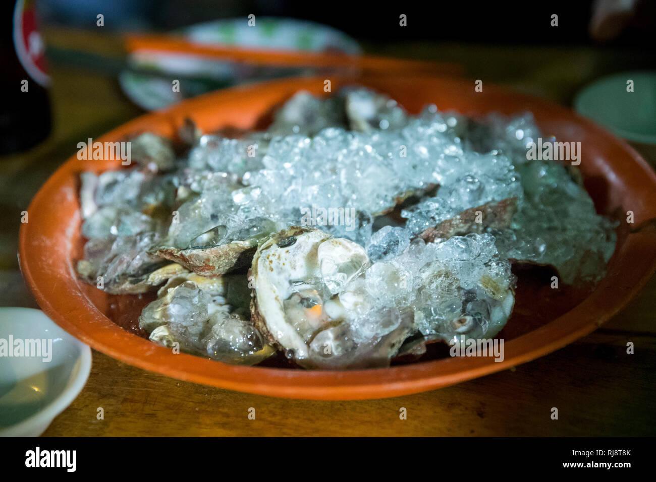 Kambodscha, Phnom Penh, Straßenrestaurant 'Oyster House', es wird auf der Straße gekocht und gegessen, sehr leckere Meeresfrüchte und Fisch, Austern a - Stock Image