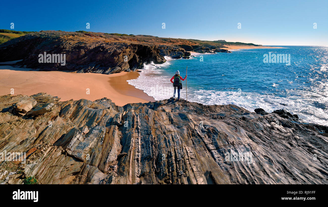 Woman in hiking outfit standing on a cliff overlooking a wild and natural beach and coast with calm blue ocean - Stock Image