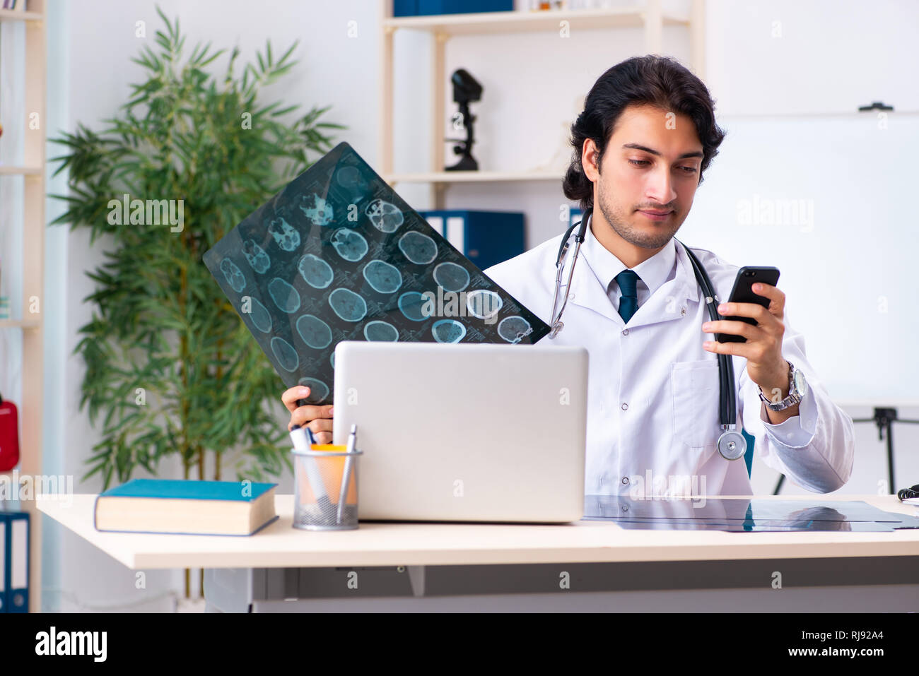 Young handsome doctor radiologist working in the clinic - Stock Image
