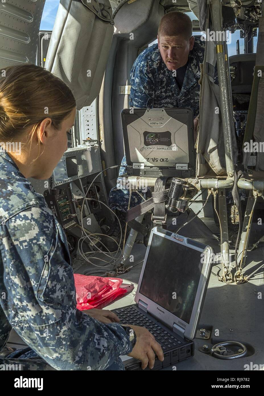 """Petty Officer 3rd Class Angela Bobst and Petty Officer 2nd Class Ryan Deppe assigned to Helicopter Sea Combat Squadron (HSC) 21 """"Blackjacks"""", review schematics on a toughbook laptop on a MH-60S Seahawk, while the helicopter is under regular maintenance check-ups on the flight line in San Diego, Nov. 4, 2016. HSC-21's mission is to provide all-weather, vertical lift, and combat-ready aircraft and crews to U.S. 7th and 5th Fleet areas of responsibility. U.S. Navy Combat Camera - Stock Image"""