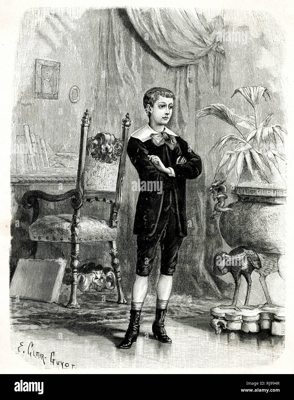 French boy wears a velvet suit comprised of knickerbockers, jacket fastened at the neck & open to reveal a waistcoat, white falling collar & large bow, socks & heeled boots. Stock Photo