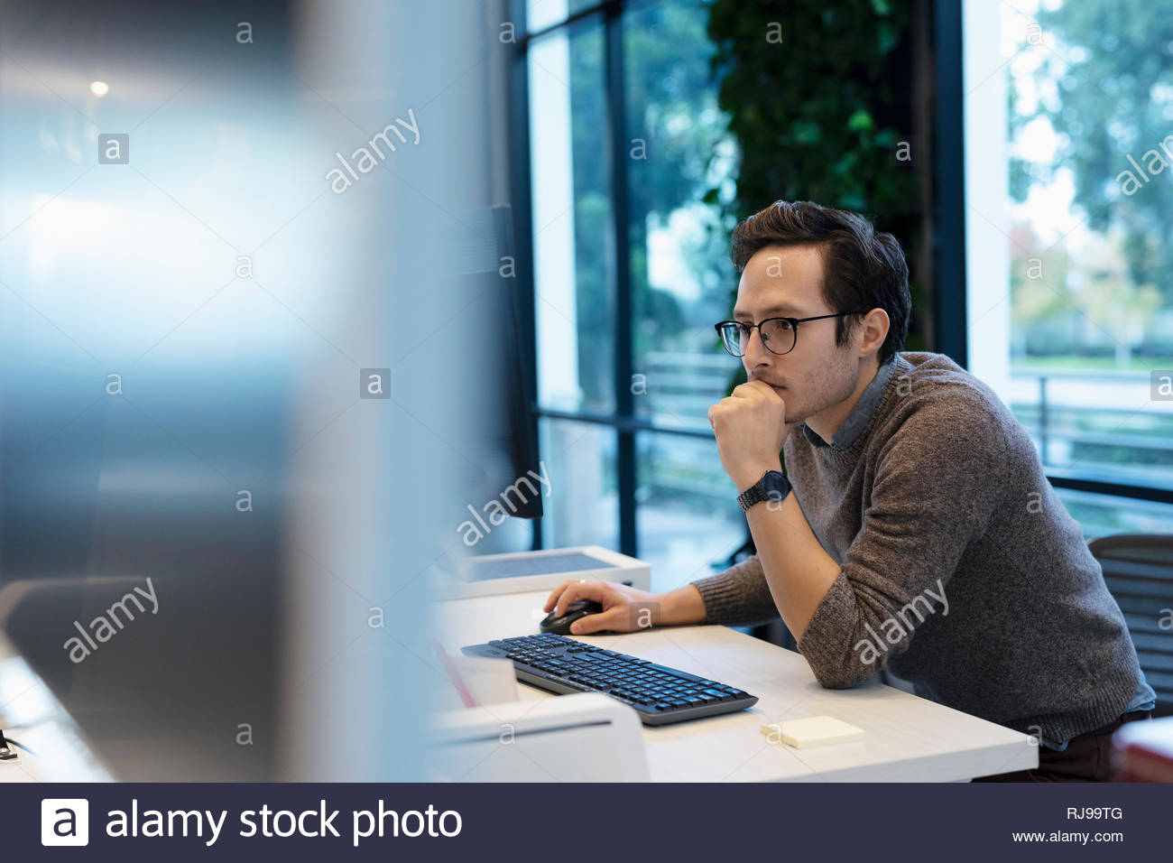 Dedicated businessman working at computer in office - Stock Image