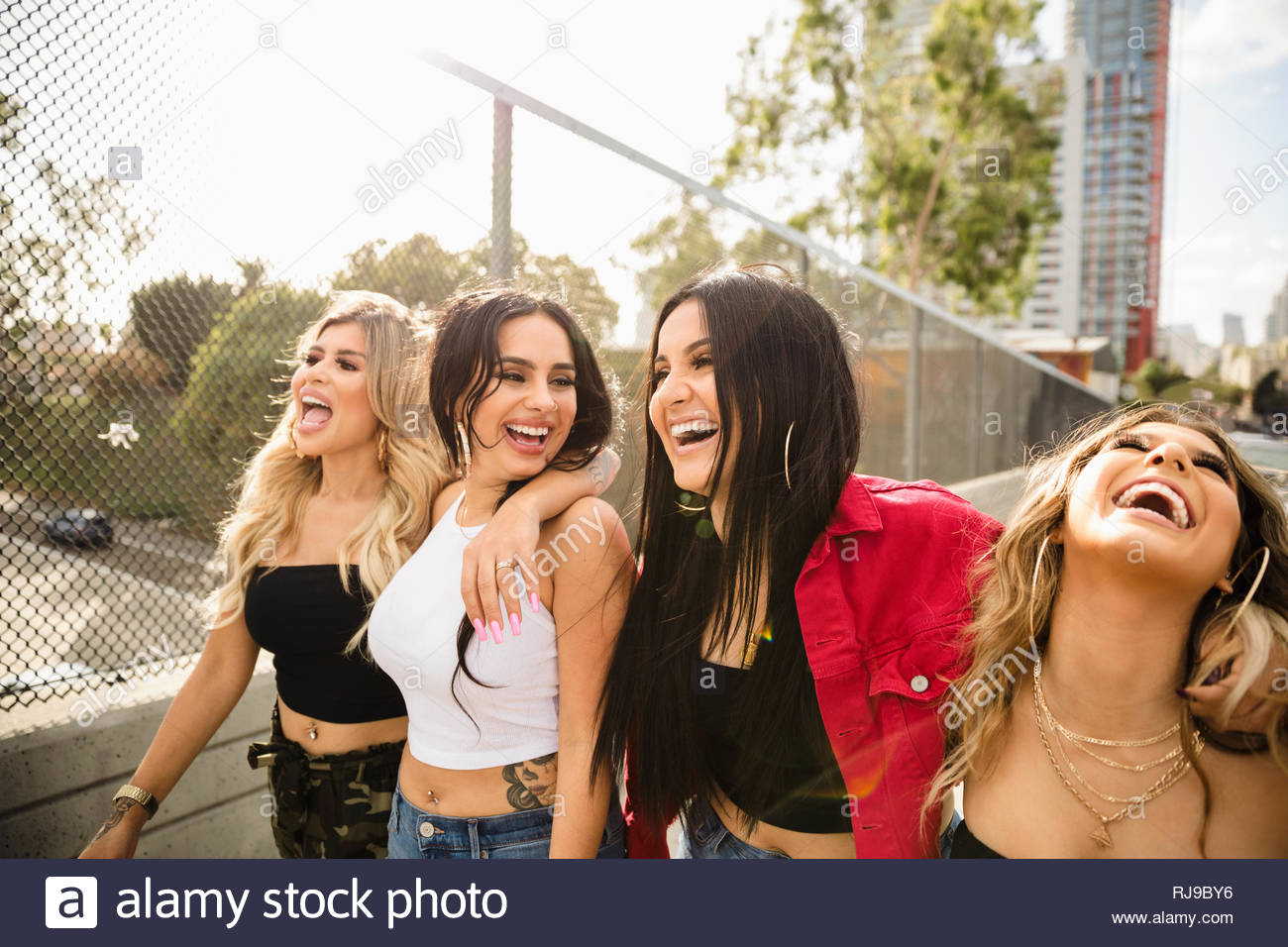 Latinx young women friends laughing and walking along overpass - Stock Image