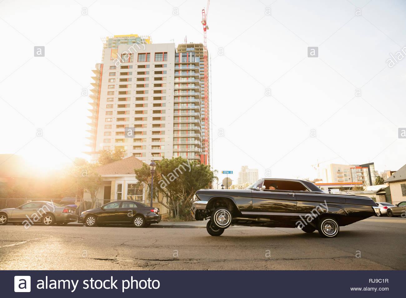 Low rider vintage car bouncing along sunny urban street - Stock Image