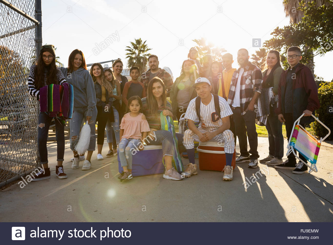 Portrait Latinx family with baseball player in sunny park - Stock Image