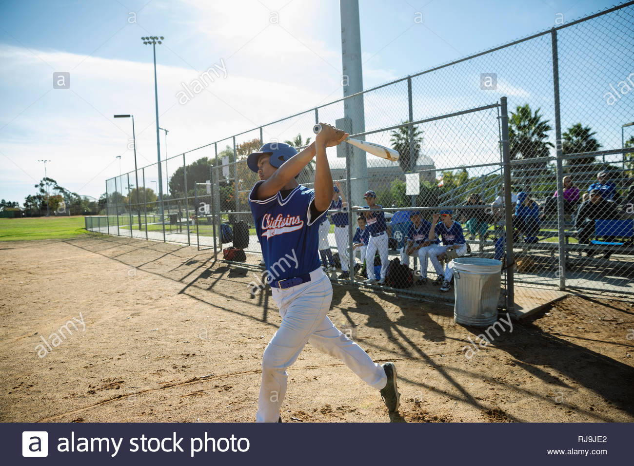 Baseball player swinging bat on sunny field Stock Photo