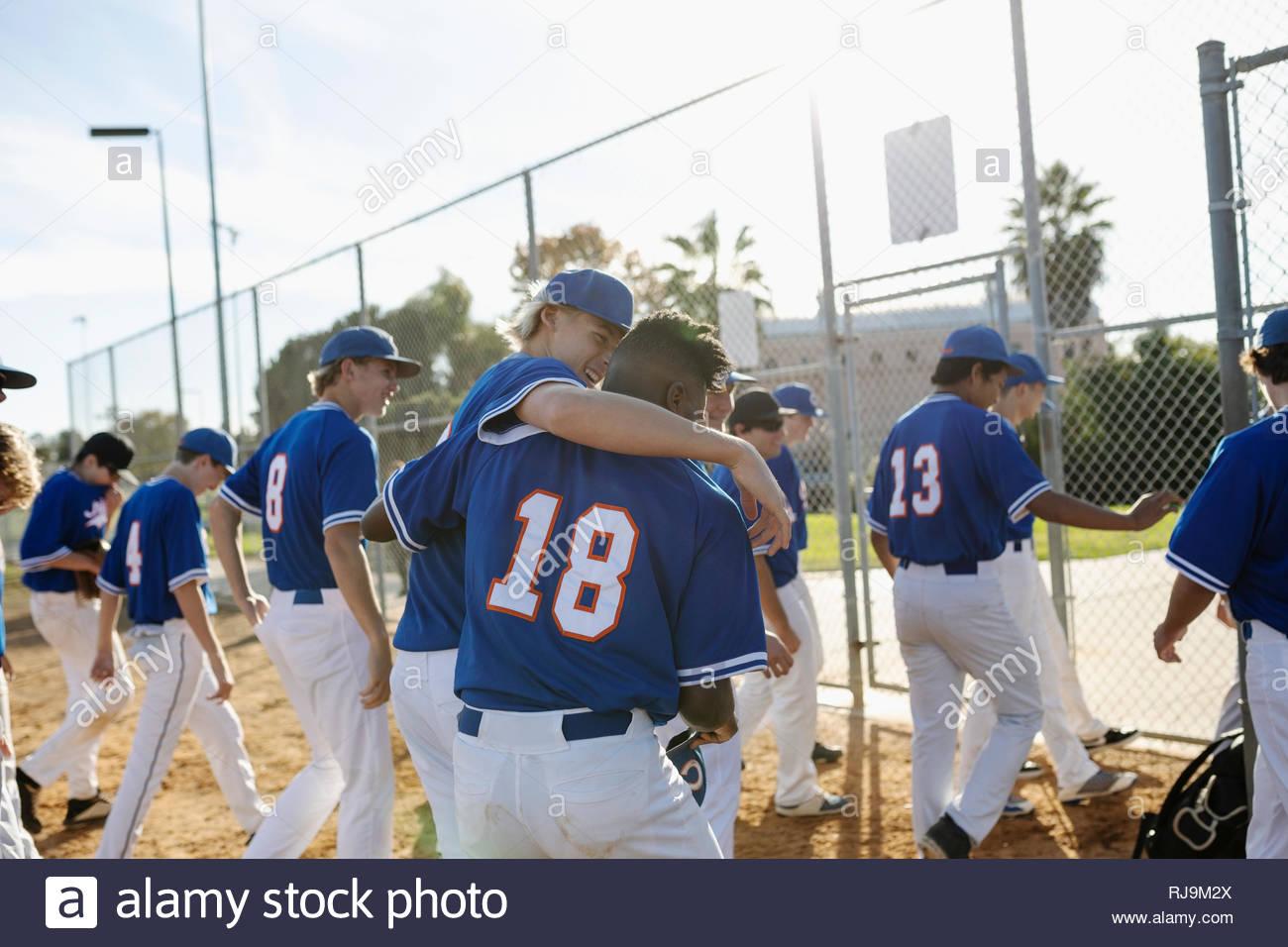 Happy baseball players hugging, walking off sunny field - Stock Image