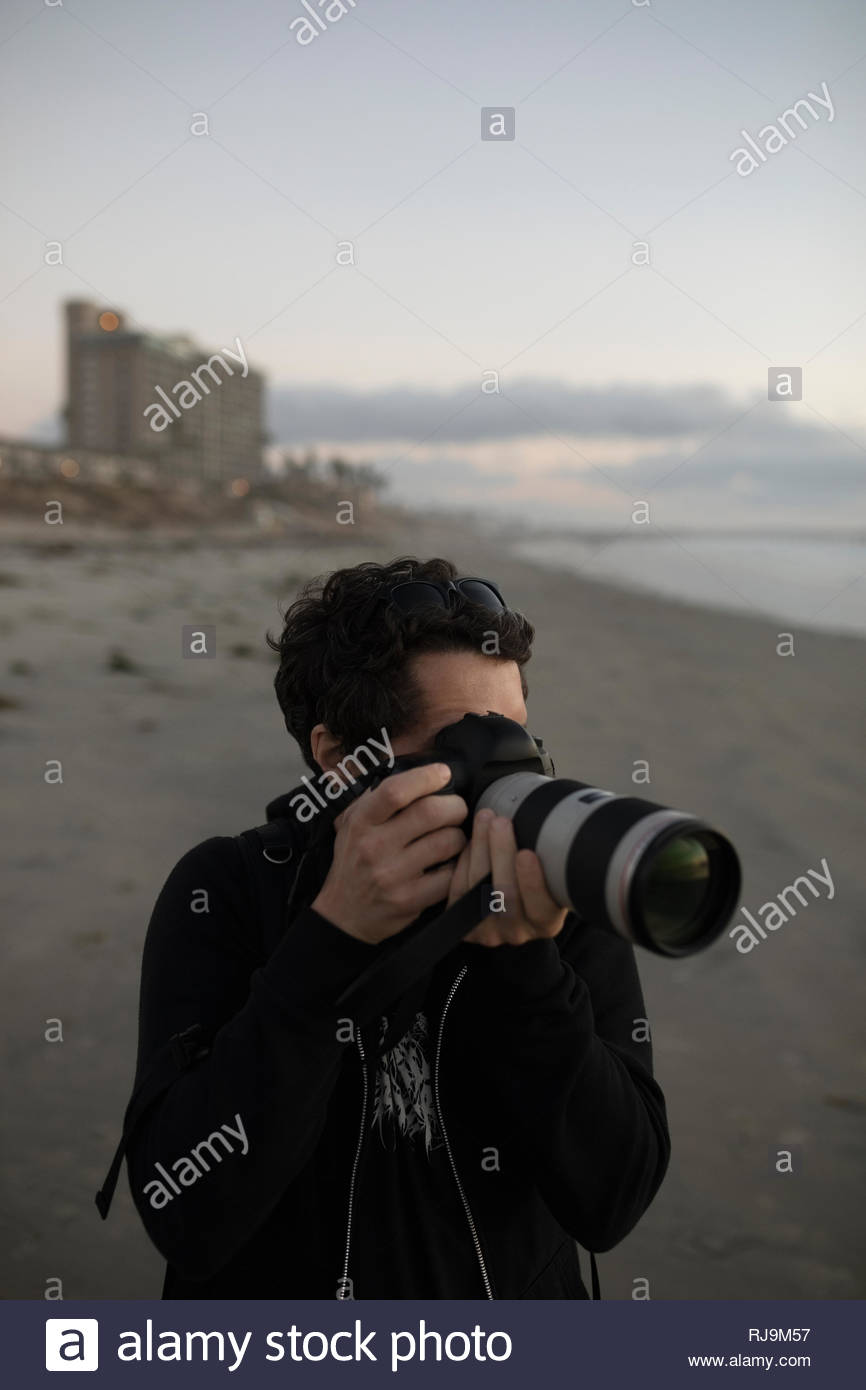 Male photographer using digital camera with lens on beach - Stock Image