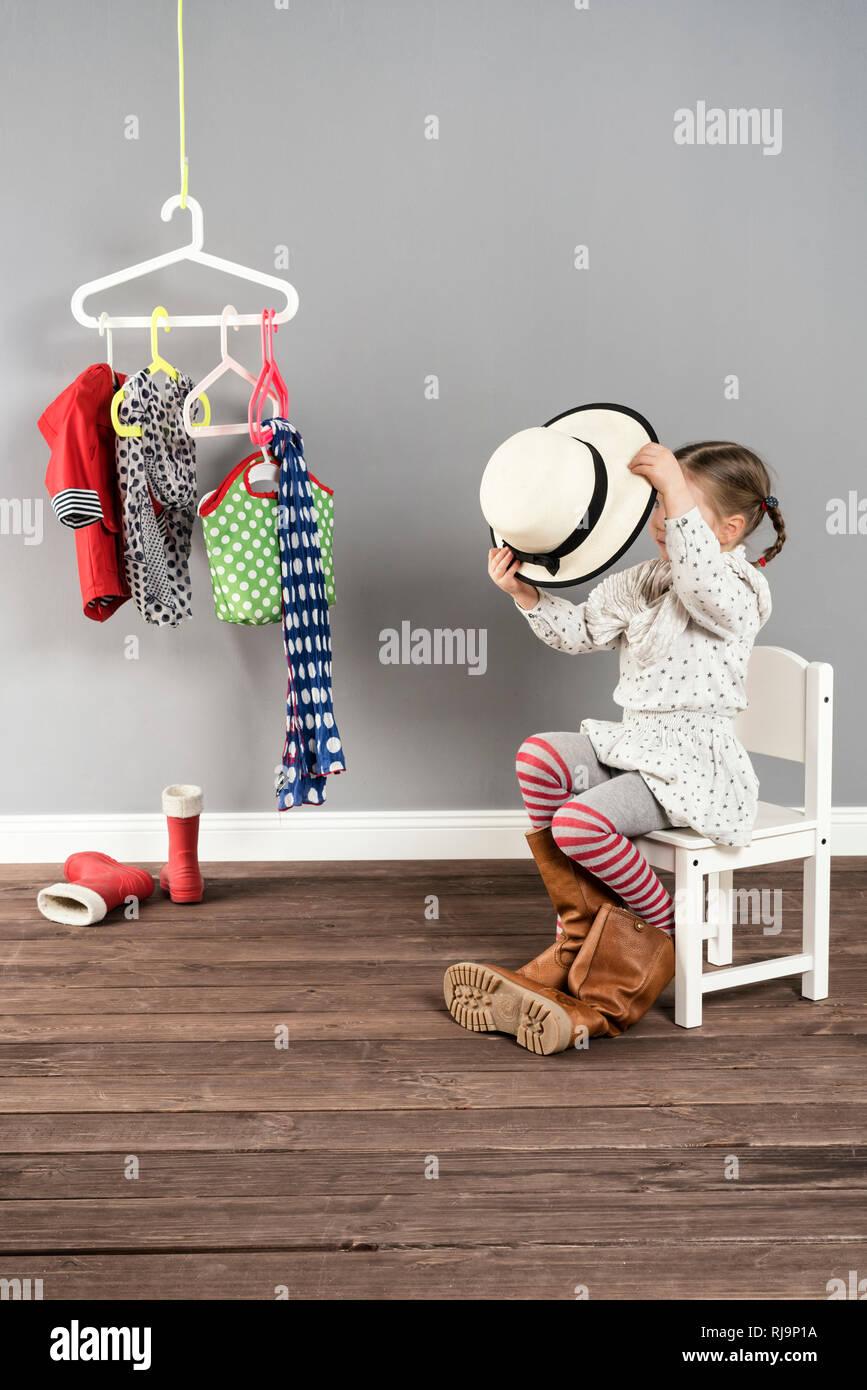 Mädchen sitzt auf einem Stuhl in der Garderobe und hat die Schuhe der Mutter an, Stock Photo